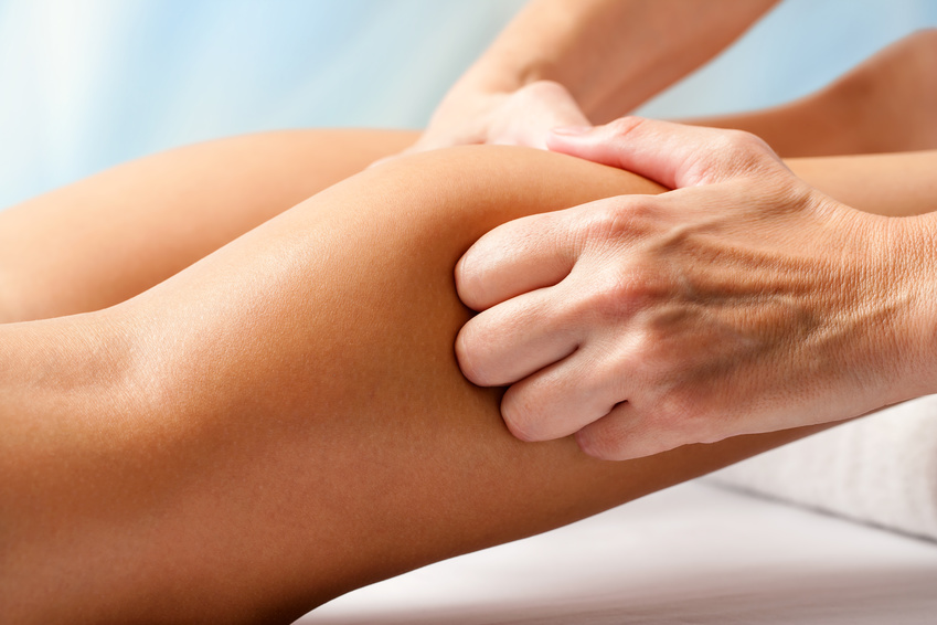 Physiotherapist hands massaging calf muscle.